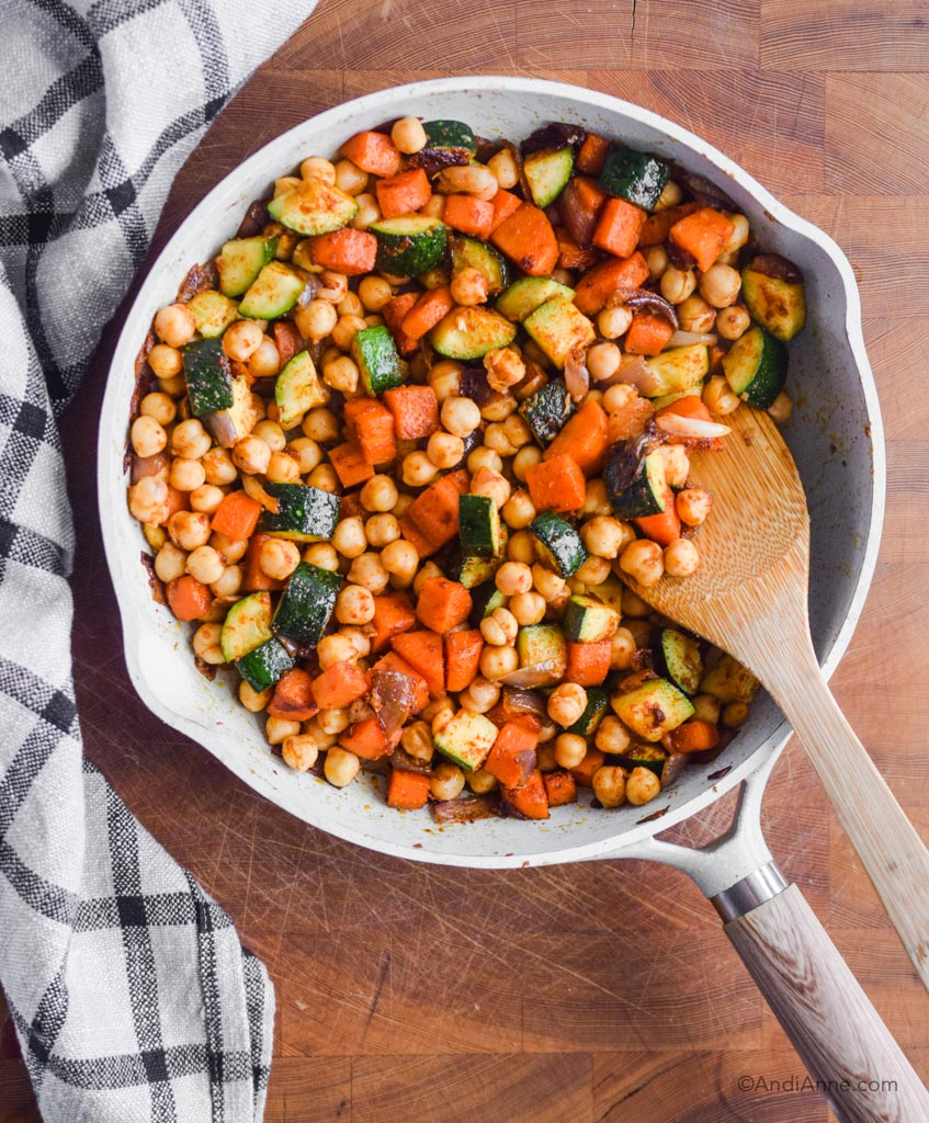 chickpeas, carrots and zucchini in frying pan with wooden spoon and kitchen towel beside it.