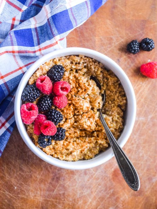 steel cut oats in a white bowl with fresh berries, cinnamon and a spoon. Blue plaid kitchen towel beside bowl.