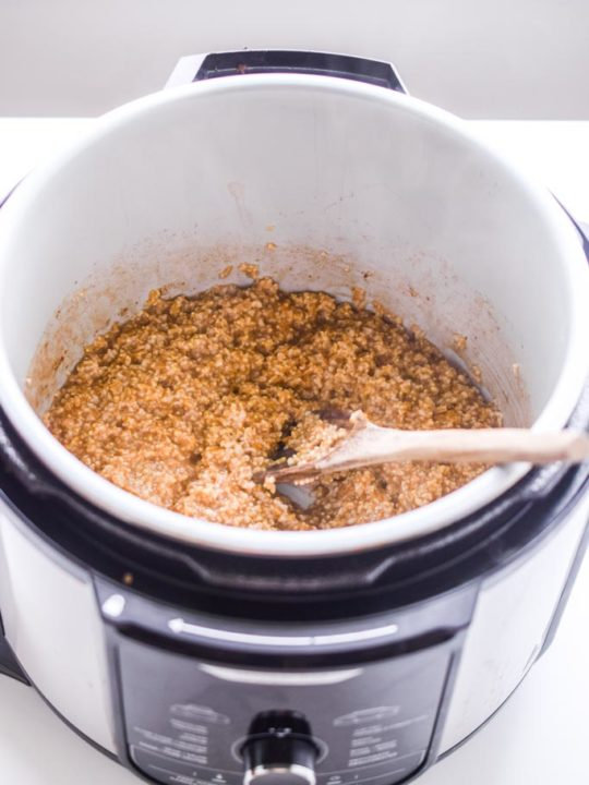 cooked steel cut oats inside an instant pot with a wooden spoon