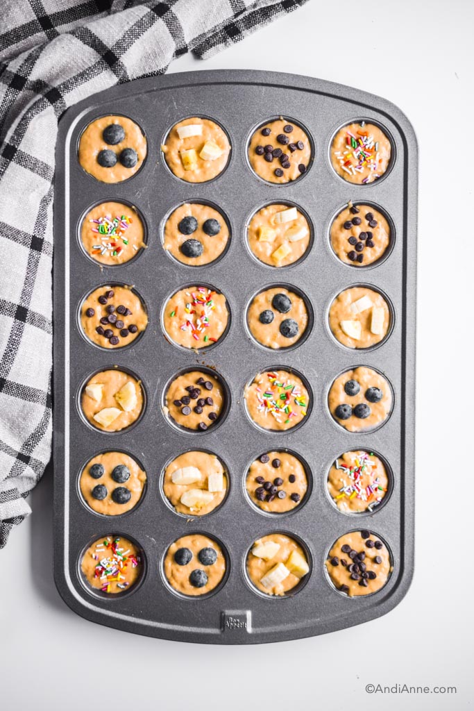 raw muffin batter inside metal mini muffin pan. berries, banana, chocolate and sprinkles top each one