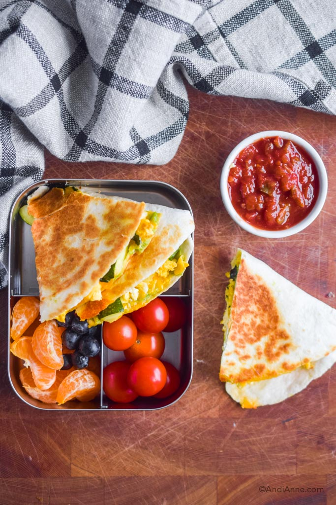 quesadilla in steel container with cherry tomatoes, oranges and grapes. Cup of salsa beside it