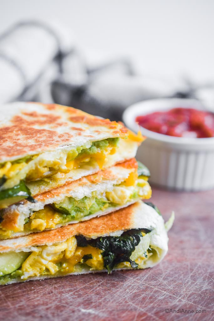 close up detail of zucchini spinach quesadilla with mashed avocado. white bowl if salsa in background.
