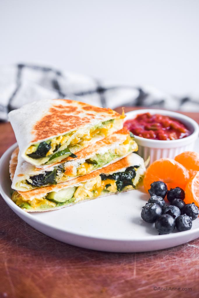 zucchini spinach breakfast quesadilla on a white plate with salsa, oranges and blueberries
