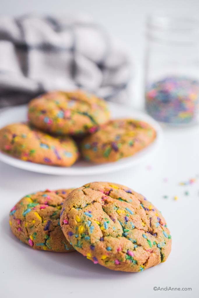 chickpea flour sprinkle cookies on a white counter with jar of sprinkles in the background