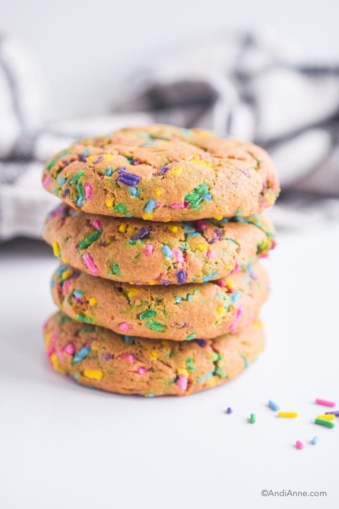 stacked chickpea sprinkle cookies with kitchen towel behind them