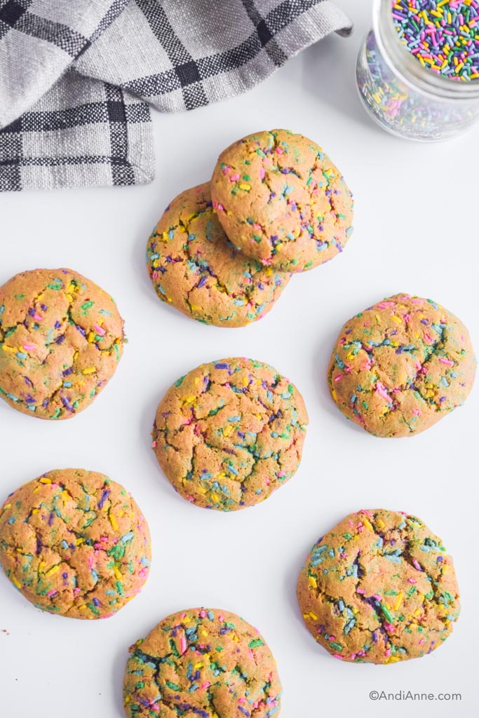 chickpea flour sprinkle cookies on a white counter with kitchen towel in and jar of sprinkles in top of photo