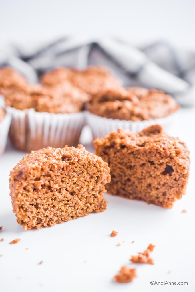 a flaxseed muffin sliced in half with more muffins behind it.