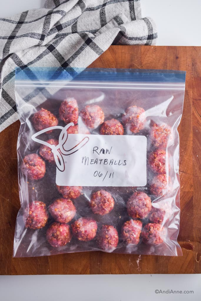 raw meatballs in a ziploc freezer bag on wood cutting board with kitchen towel beside it