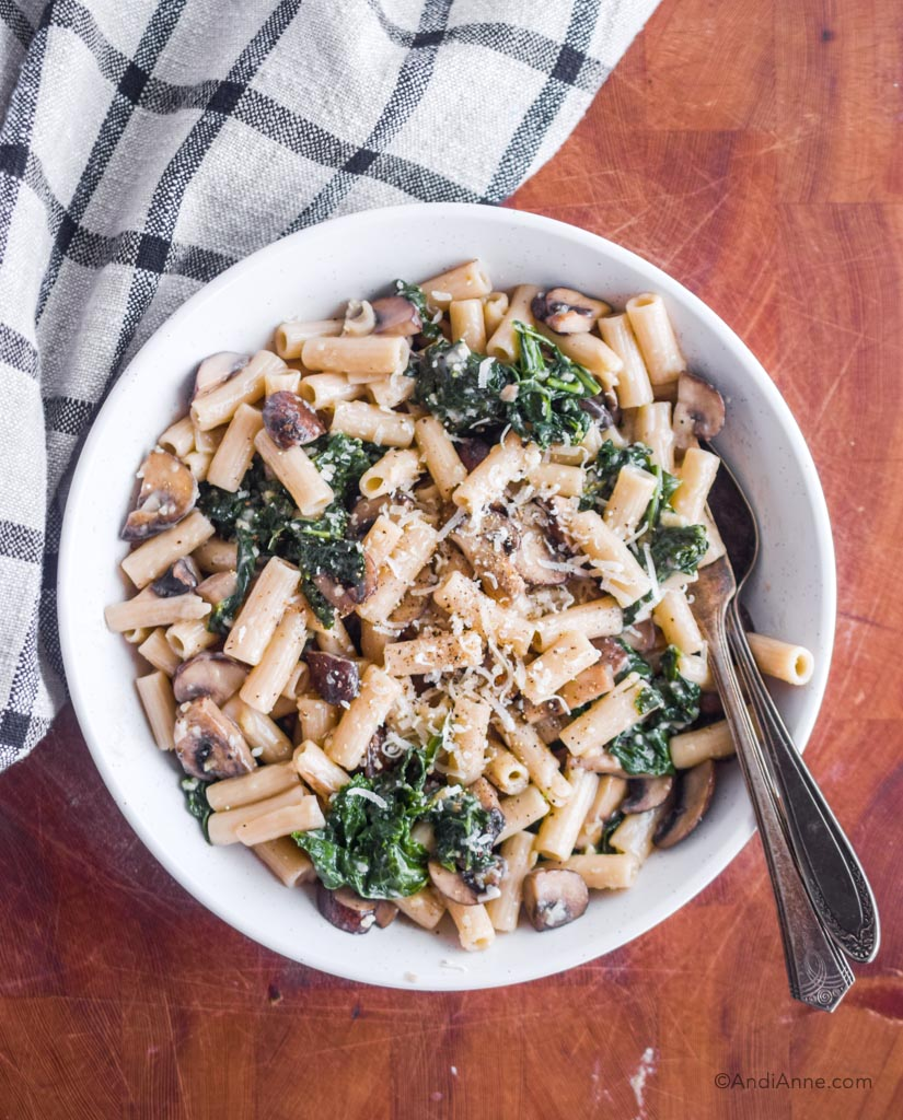 brown rice penne pasta with parmesan, kale and mushrooms in a white bowl with silver spoon and fork on the side.