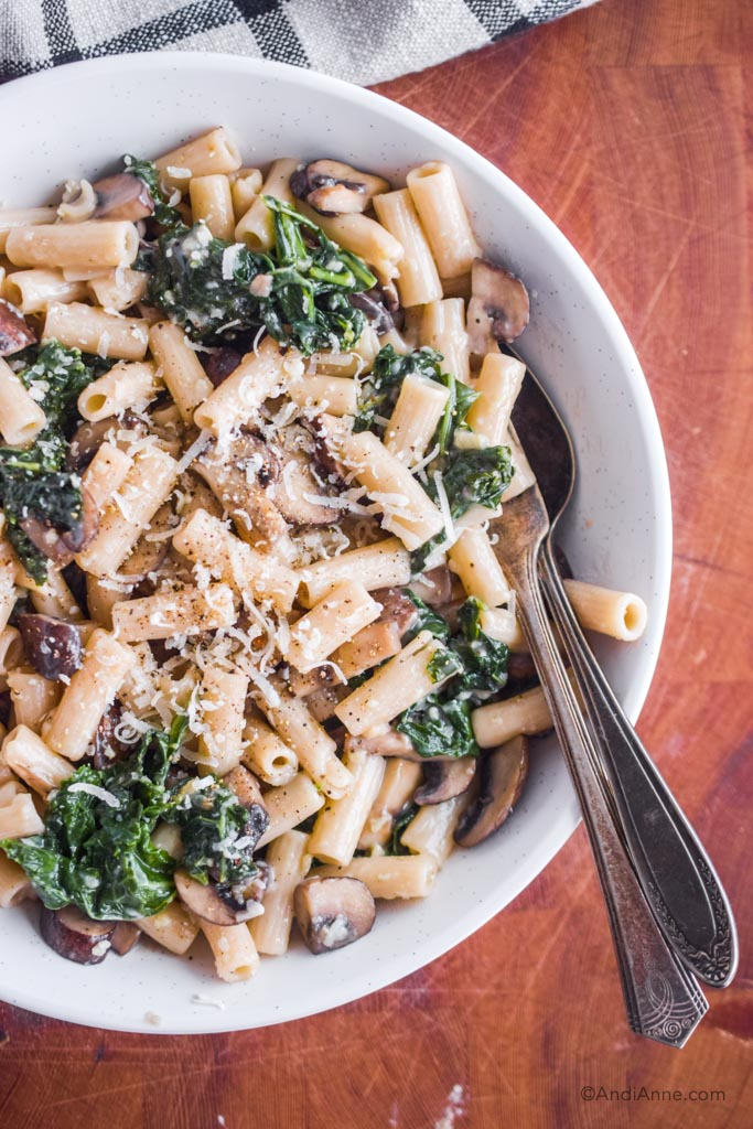 mushroom kale pasta with parmesan cheese in a white bowl. On wood cutting block with kitchen towel in corner.