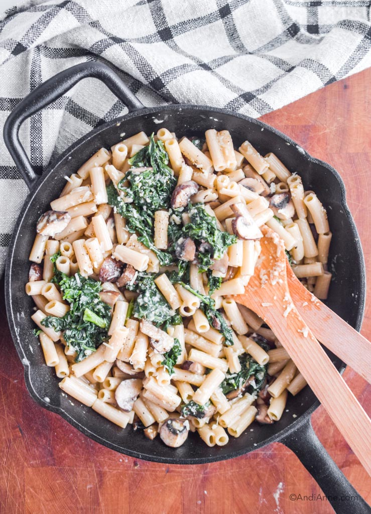 penne pasta with kale, mushrooms and parmesan cheese in a cast iron skillet and two wooden spoons. Pan on a wood board with kitchen towel in corner.