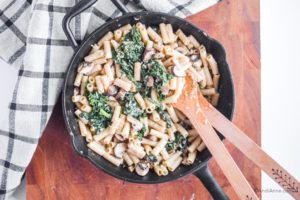 cooked pasta, kale and mushrooms with parmesan cheese in a frying pan. Two wooden spoons on the side.