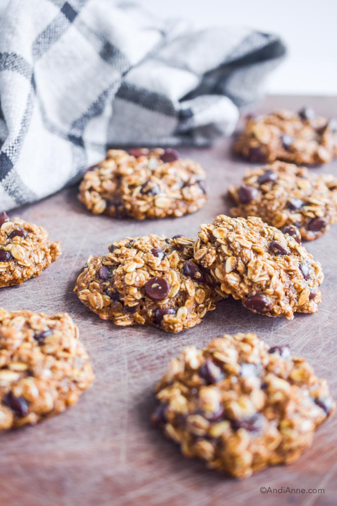 oatmeal chocolate chip cookies on a wood cutting board with kitchen towel behind it