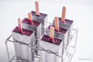 steel popsicle mold with wood sticks and blueberry puree inside it