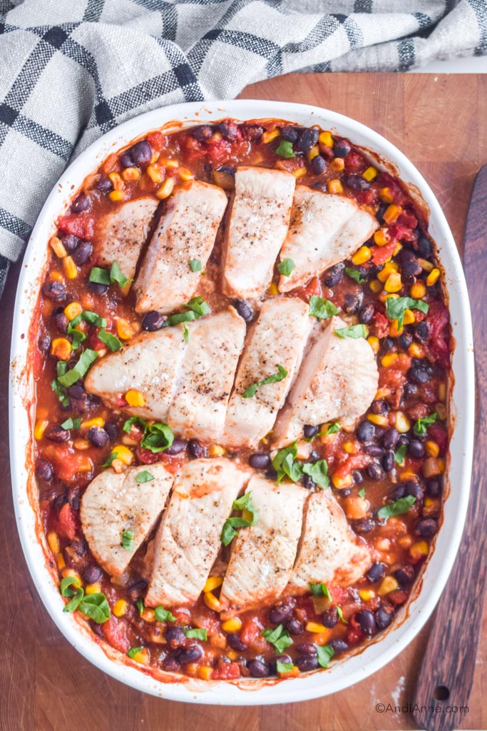 dump and bake salsa chicken recipe inside an oval baking dish. On top of a cutting board with kitchen towel.