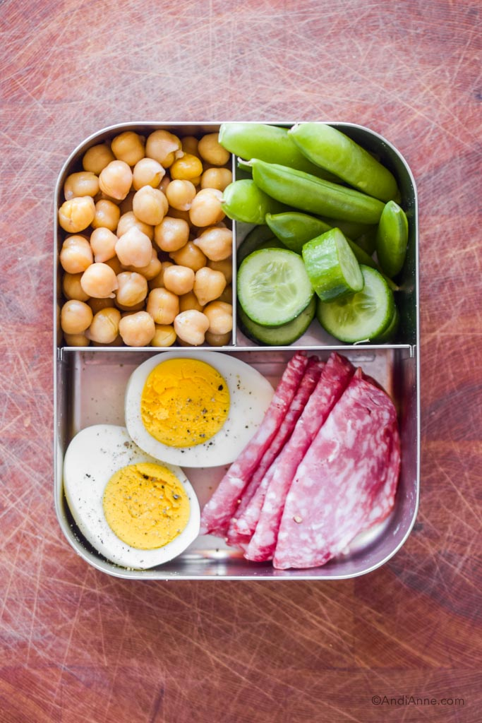 Stainless steel bento box lunch with sliced hard boiled egg, salami slices, snap peas, chickpeas and cucumber slices.