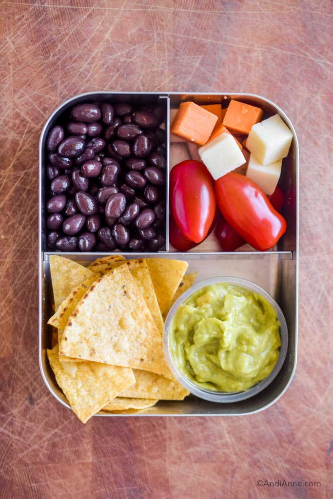 Stainless steel bento box lunch with black beans, grape tomatoes, cheese cubes, tortilla chips and small container of guacamole.
