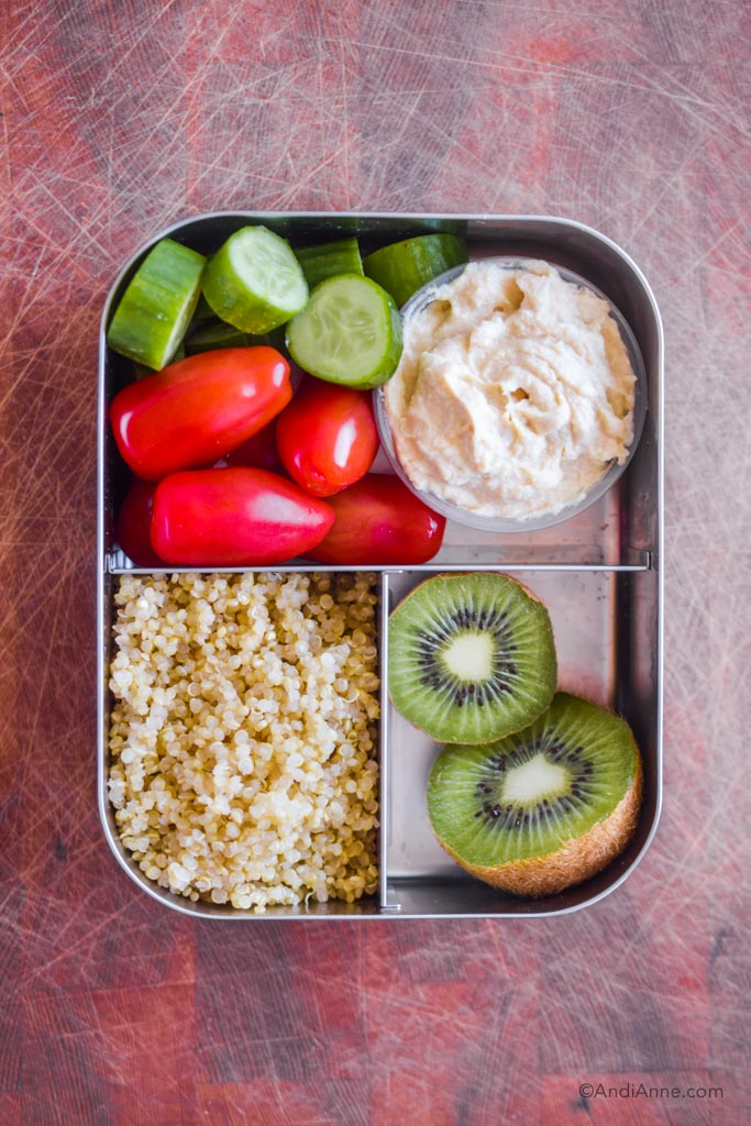 Stainless steel bento box lunch with quinoa, kiwi slice, grape tomatoes, cucumber slices, and hummus.