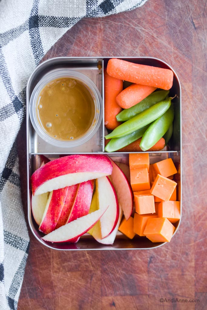 Stainless steel bento box lunch with apple slices, cheese cubes, carrots, snap peas, and a small container of seed butter.