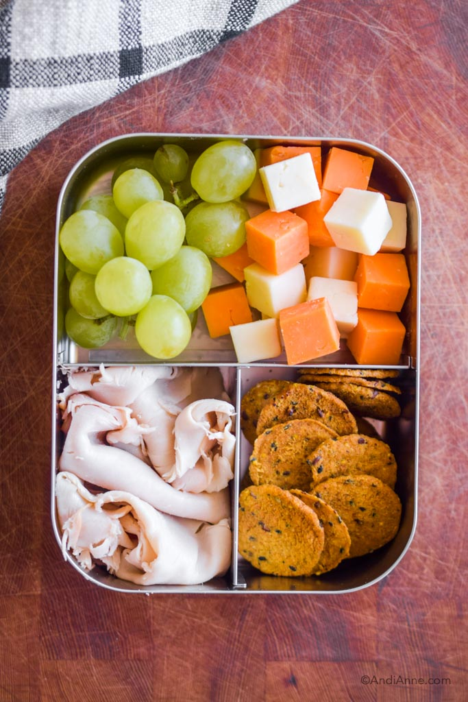 Stainless steel bento box lunch with deli turkey slices, crackers, grapes and cheese cubes.