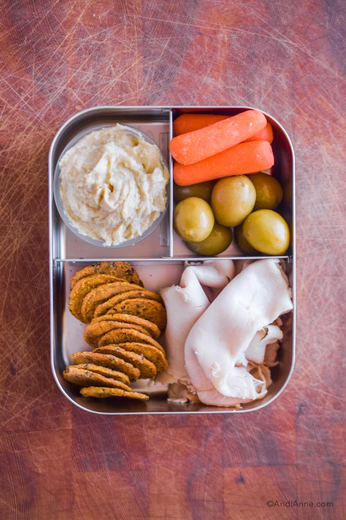 Stainless steel bento box lunch with deli turkey slices, handful of crackers, baby carrots, olives and small container of hummus.
