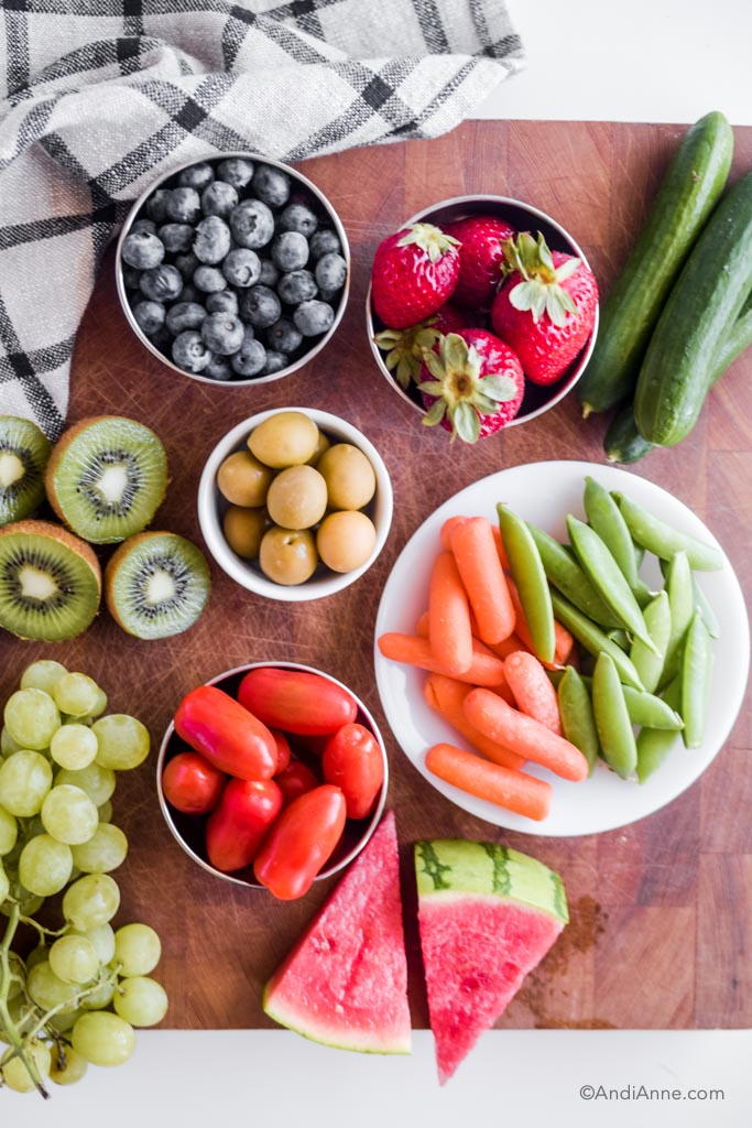 bowls of raw fruits and vegetables sitting on a wood cutting board.