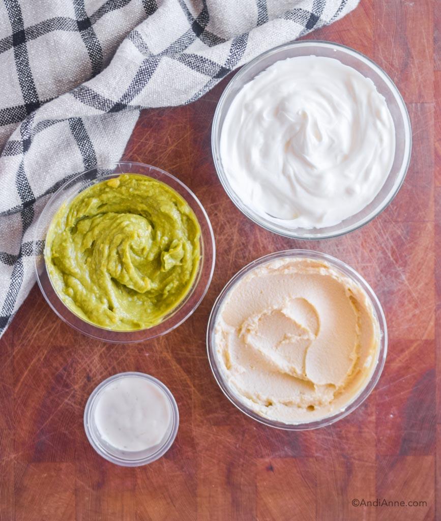 four bowls on a wood cutting board. One with guacamole, greek yogurt, hummus and ranch dip.