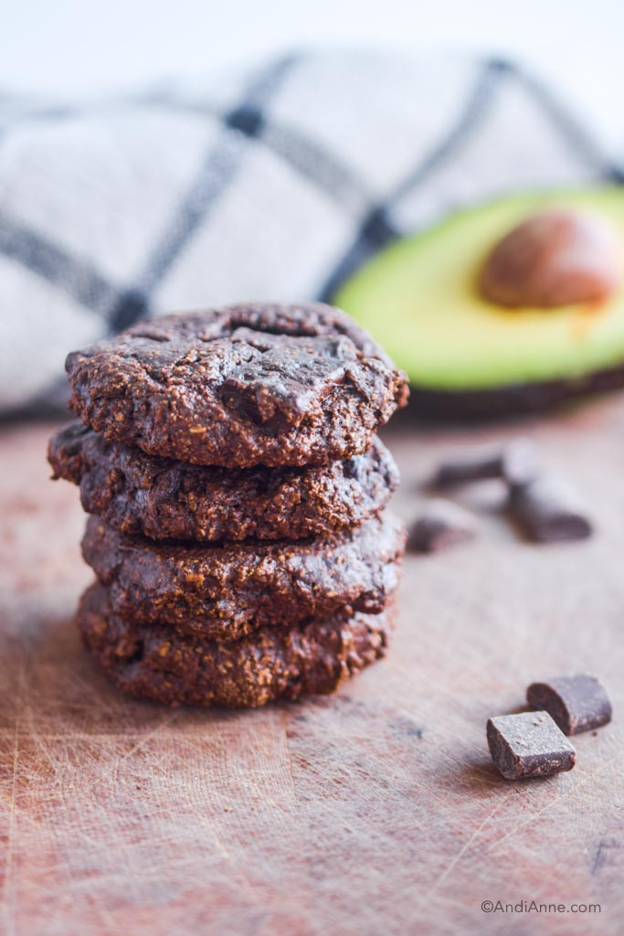 chocolate avocado cookies stacked on top of eachother. Sliced avocado in background.