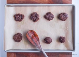 raw cookies on a baking sheet being flattened with back of a wooden spoon