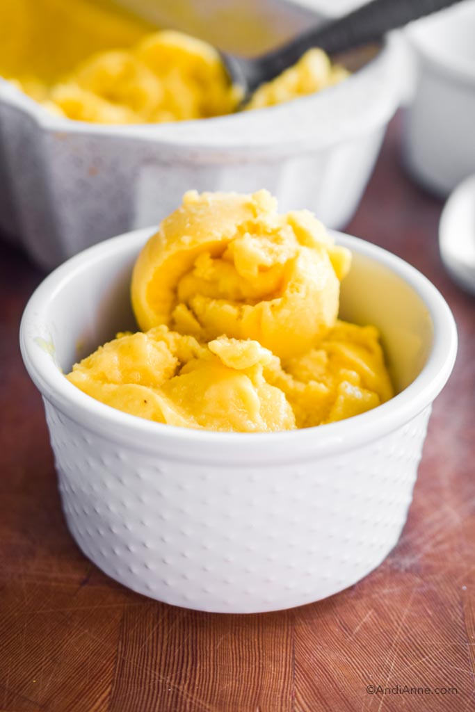 frozen mango ice cream in a white bowl. Dish with rest of mango ice cream and ice cream scoop are in the background.