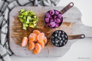 kiwi, raspberries, mandarin orange slices and blueberries on a cutting board