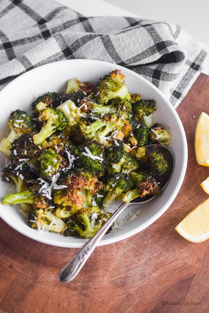 air fryer broccoli in a white bowl with a large silver spoon. Sliced lemons and a kitchen towel surround the bowl.