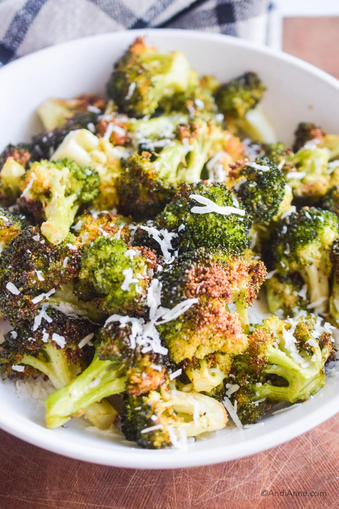 Close up of air fryer broccoli with grated parmesan cheese in white dish