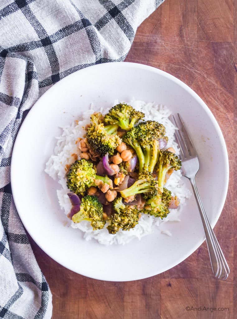 rice and broccoli chickpea stir fry in a white dish with a fork. Dish is on a wood cutting board with kitchen towel beside it.