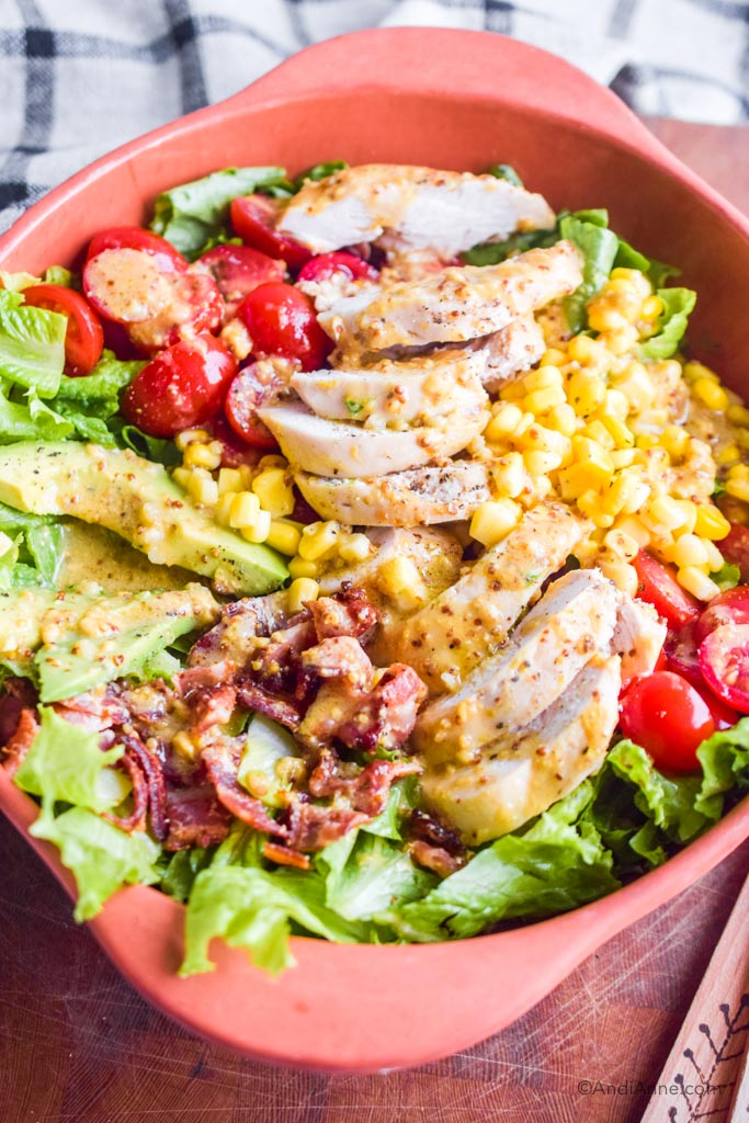 close up detail of maple dijon chicken avocado salad with dressing drizzled overtop.
