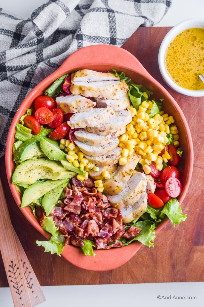 maple dijon chicken avocado salad in a terra cotta bowl with dressing in white bowl beside it.