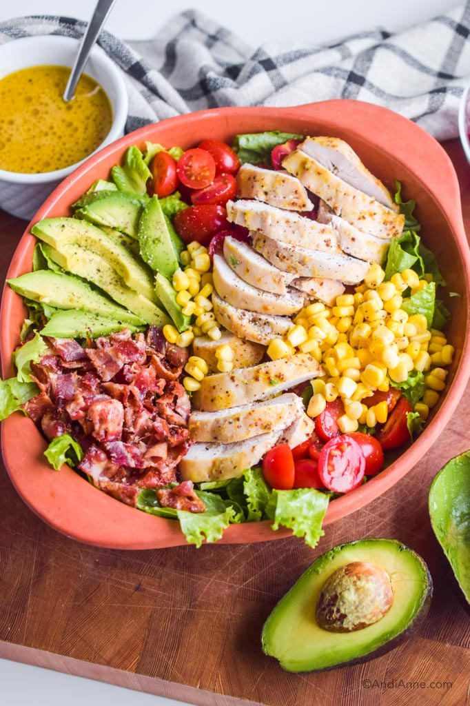 maple dijon chicken avocado salad in bowl. White bowl of dressing with spoon and avocado sliced in half surround it.