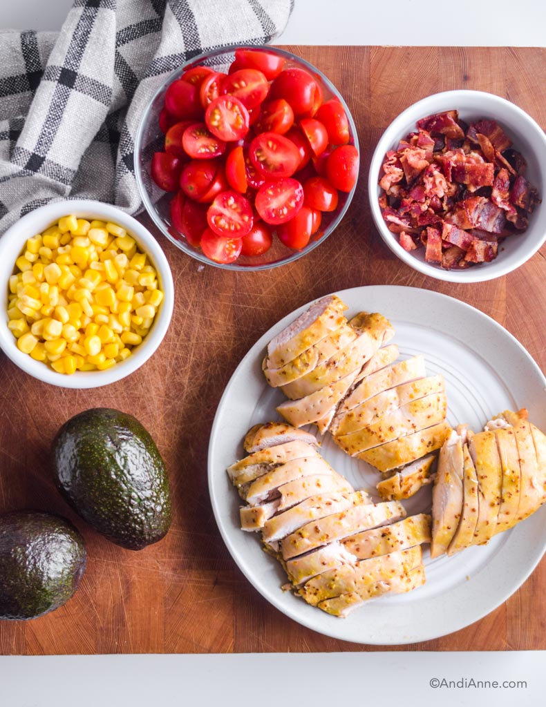 Plate of sliced chicken, two avocados, bowl of corn, bowl of sliced cherry tomatoes and bowl of chopped bacon.
