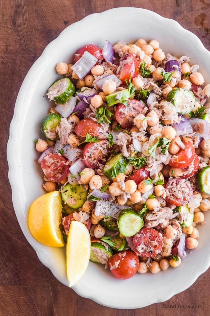 chickpea lemon tuna salad in white bowl with lemon wedges