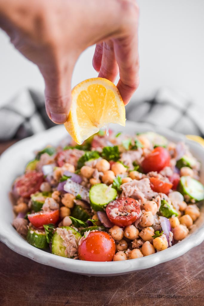 hand squeezing lemon overtop of chickpea tuna salad in a white bowl