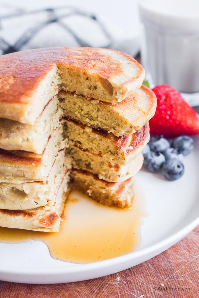 Stack of pancakes cut through. Berries in background.
