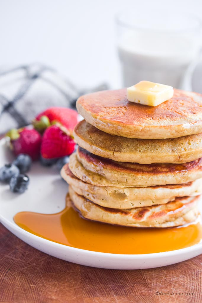 stack of quinoa flour pancakes with butter and maple syrup poured on. Berries in background
