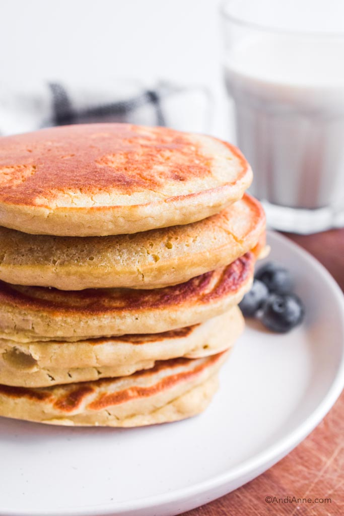 stack of quinoa flour pancakes on white plate. Glass of milk in background.