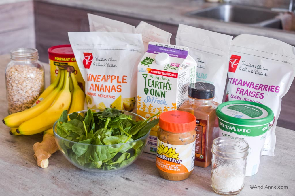ingredients to make smoothie packs on a counter, including frozen fruit bags, a bowl of spinach, bananas, milk, cinnamon, yogurt and nut butter