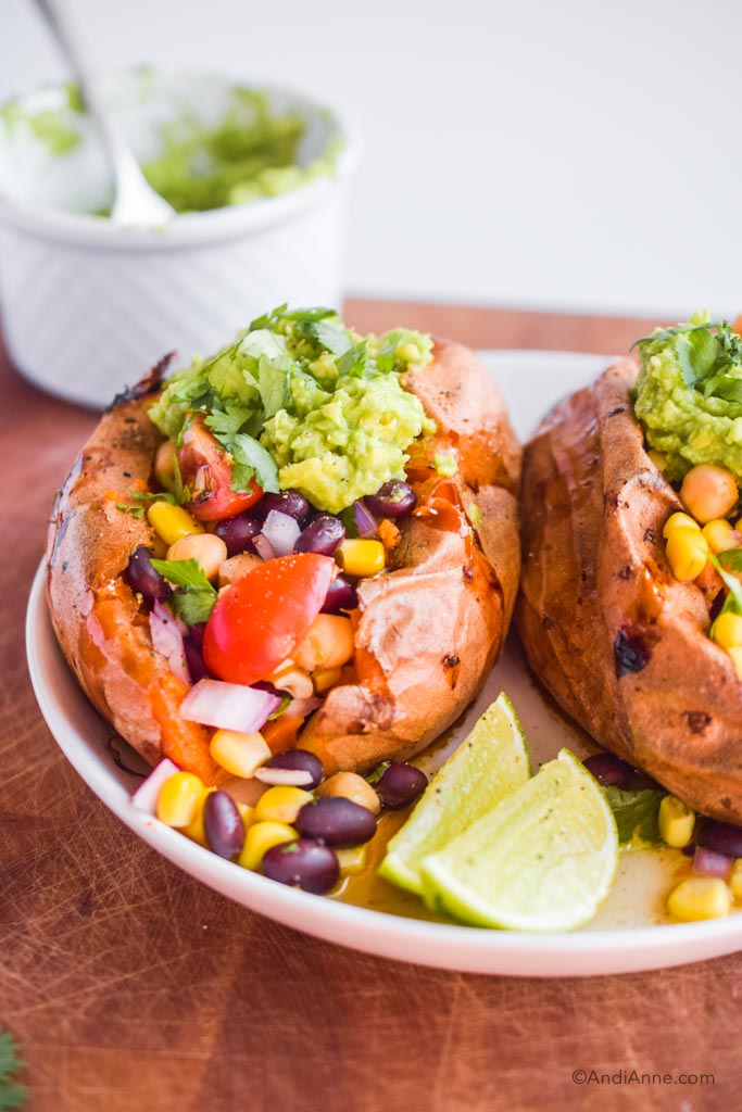 Taco stuffed sweet potatoes on a white plate with two limes. White bowl in the background.
