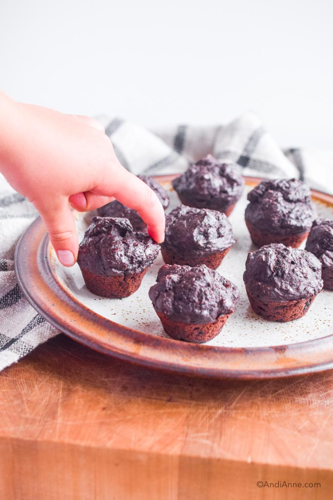 kids hands picking up a mini muffin from a brown plate