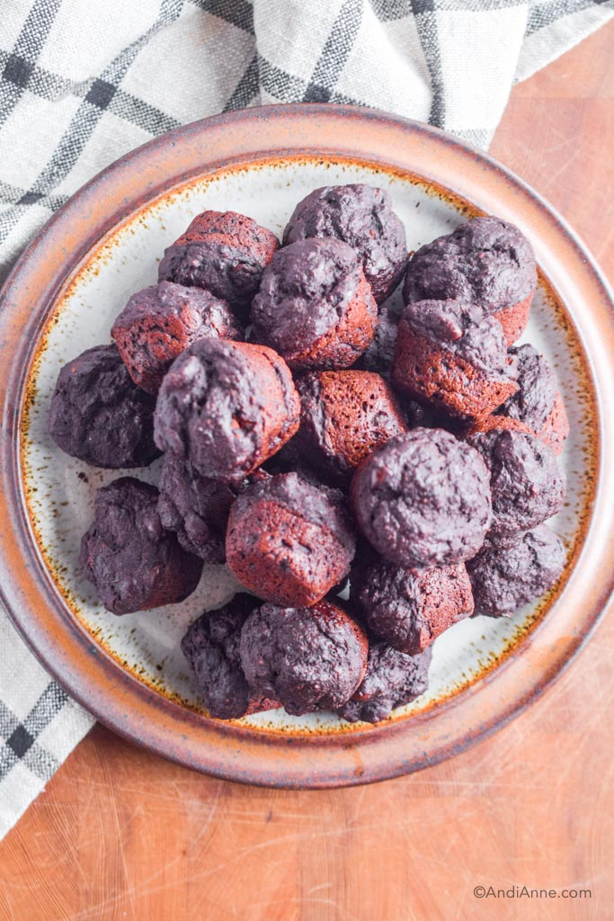 chocolate protein mini muffins on a large brown plate with kitchen towel beside it