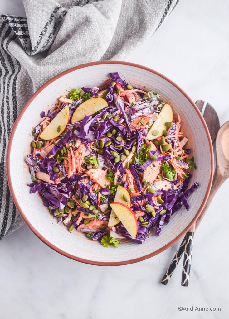Carrot apple cabbage coleslaw in a white bowl with serving spoons on the side.