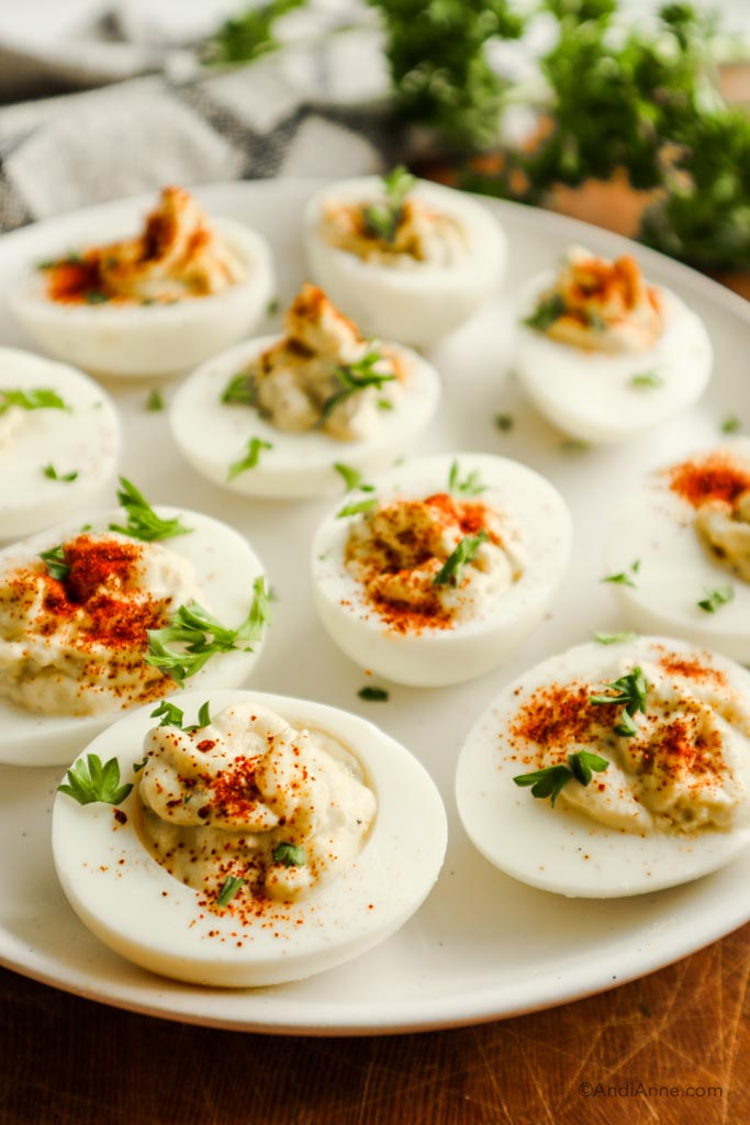 side angle of deviled eggs on plate sprinkled with chopped parsley