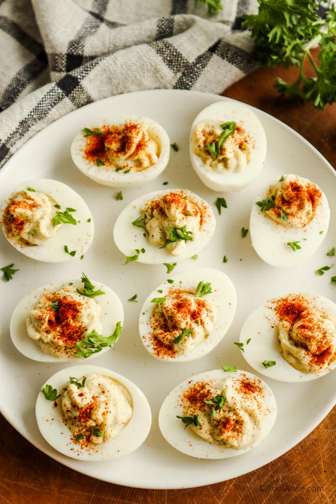 Deviled eggs on a white plate sprinkled with paprika and parsley.